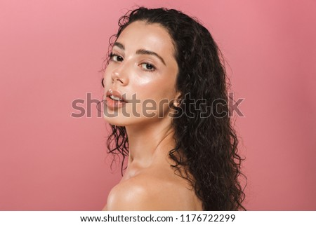 Beauty portrait of a seductive young topless woman with curly brunette hair posing over pink background