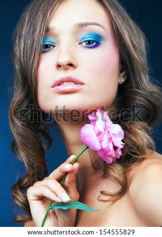 Beauty portrait of a sensual Caucasian woman. She holds a rose in his hand near his face.