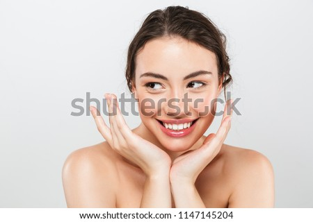Beauty portrait of a smiling young topless woman with make-up looking away isolated over gray background #1147145204