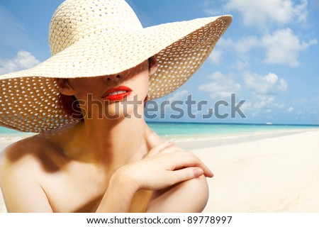 Beauty portrait of a woman wearing straw hat on the white sand beach