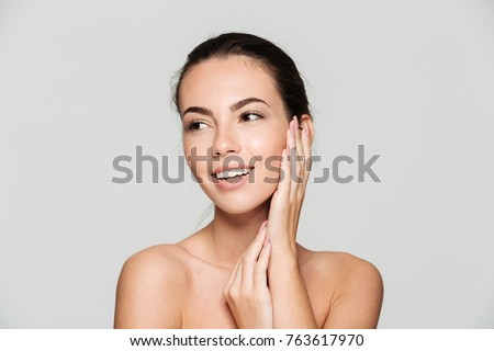 Beauty portrait of a young attractive half naked woman with perfect skin posing and looking away isolated over white background