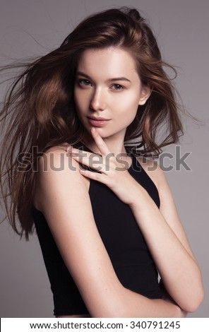 beauty portrait of a young beautiful brunette girl with long black straight flying hair. Magnificent hair. #340791245