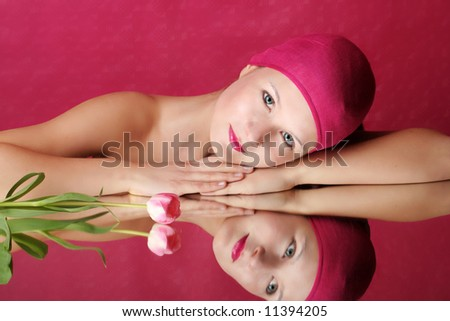 beauty portrait of a young woman in pink with a tulip flower on a mirror