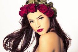 beauty portrait of a young woman with a wreath of red roses on her head