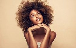 Beauty portrait of african american black  woman with clean healthy skin on beige background. Smiling dreamy beautiful afro girl.Curly  hair