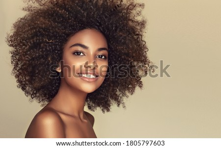 Beauty portrait of african american black  woman with clean healthy skin on beige background. Life style and cosmetic. Smiling beautiful afro girl.Curly  hair  Foto stock ©