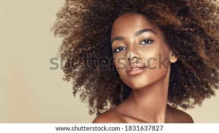 Beauty portrait of african american girl with clean healthy skin on beige background. Smiling dreamy beautiful black woman.Curly  hair in afro style  Foto stock ©