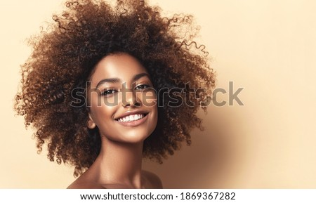 Beauty portrait of african american girl with clean healthy skin on beige background. Smiling dreamy beautiful black woman.Curly hair in afro style