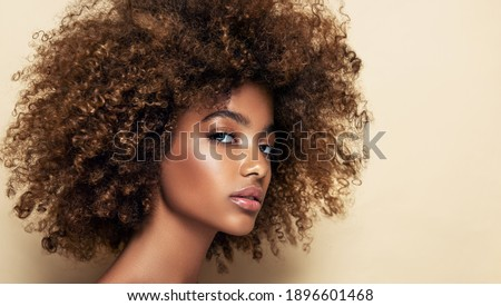 Beauty portrait of african american girl with clean healthy skin on beige background. Smiling dreamy beautiful black woman.Curly hair in afro style ストックフォト ©