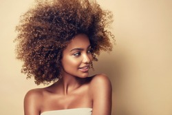 Beauty portrait of african american woman with clean healthy skin on beige background. Skin care and beauty concept. Smiling beautiful afro girl.Curly black hair