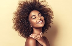 Beauty portrait of african american woman with clean healthy skin on beige background. Smiling dreamy beautiful afro girl.Curly black hair