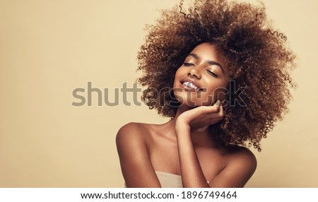 Beauty portrait of african american woman with clean healthy skin on beige background. Smiling beautiful afro girl.Curly black hair