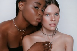Beauty portrait of africans and europeans girls in jewelry on neck and fashionable make up stand close to each other on a white background. Two beautiful girls of different races dark skinned and whit