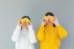 Beauty portrait of an attractive healthy two young women posing with an orange isolated over gray background