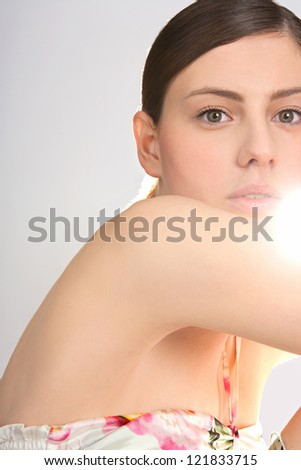 Beauty portrait of an attractive young woman looking at the camera with direct sun light filtering through her face with perfect skin.