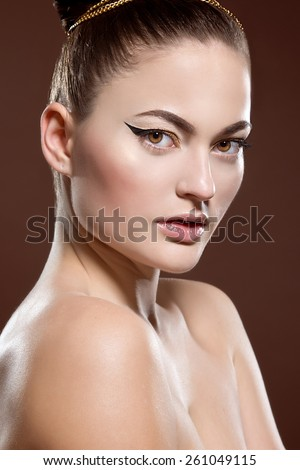 Beauty portrait of attractive model face with bright visage. Gold eye makeup and soft beige lips make-up. Gold arrow make up
