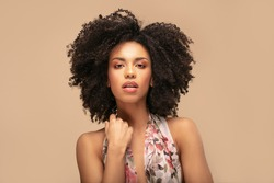 Beauty portrait of beautiful emotional african american girl with curly hair on beige studio background.