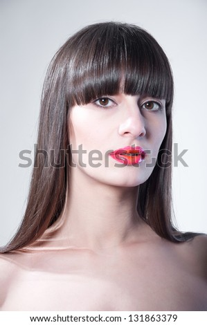 Beauty portrait of beautiful pround young woman with healthy straight hair, long straight fringe, natural makeup, bright colorful red glossy lips, looking at camera. Light gray background, copy space