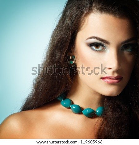 Beauty portrait of beautiful young fresh woman with long brown healthy hair. Over mint background - stock photo