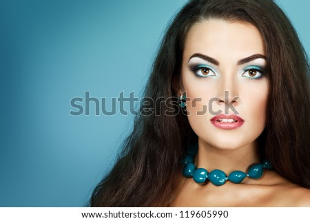 Beauty portrait of beautiful young fresh woman with long brown healthy hair. Over turquoise background