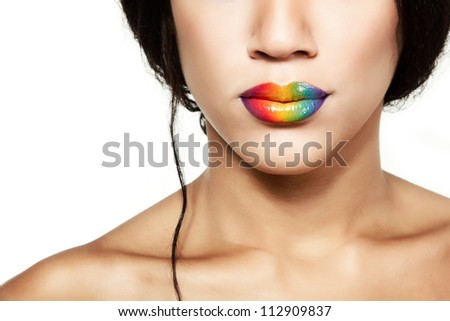 Beauty portrait of beautiful young mulatto fresh woman with rainbow lipstick, detail of face and shoulders closeup over white background