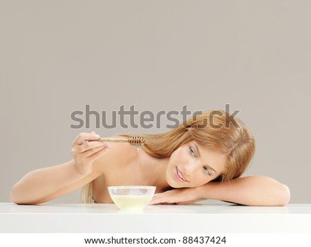 beauty portrait of blonde woman with honey bowl, smiling