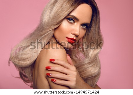 Beauty portrait of blonde woman with red lips, long healthy shiny blond hair style and manicured nails looking at camera. Sensual girl with bright makeup isolated on pink studio backhround.