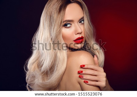 Beauty portrait of blonde woman with red lips, long healthy shiny blond hair style and manicured nails looking at camera. Sensual girl with bright makeup isolated on dark studio backhround.
