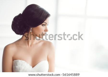 Beauty portrait of bride wearing fashion wedding dress with feathers with luxury delight make-up and hairstyle, studio indoor photo. Young attractive multi-racial Asian Caucasian model. Profile of