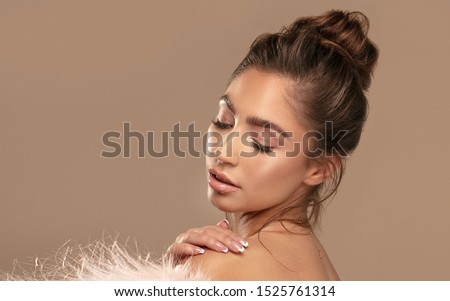 Beauty portrait of elegant young brunette girl wearing pink eco fur. Attractive woman in delicate glamour makeup.