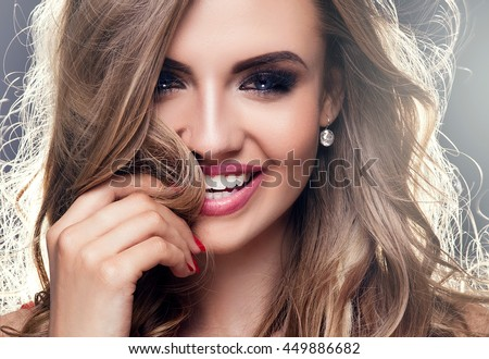 Beauty portrait of elegant young woman. Dark background. Girl looking at camera. Glamour makeup.