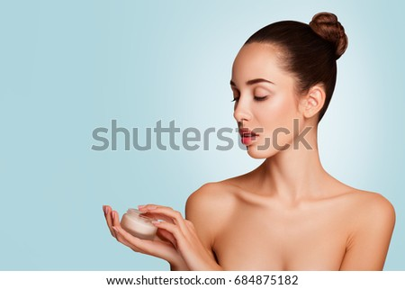 Beauty Portrait of Girl with Perfect Nude Make-up. Holding Cream, Some Cream on Finger. Looking for a Cream. Beauty Salon. Head and Shoulders, Studio, indoors . beautiful makeup expressive cheekbones