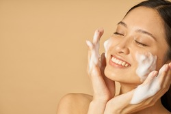 Beauty portrait of lovely young woman smiling with eyes closed while applying gentle foam facial cleanser isolated over beige background