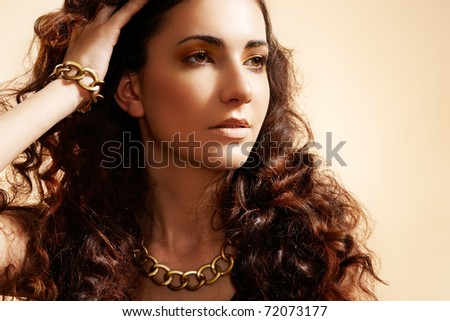 Beauty portrait of luxury fashion woman with glamour gold jewellery, curly hairstyle  on beige background. Accessories and jewelry. - stock photo