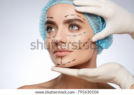 Beauty portrait of woman in blue cap looking aside, plastic surgery concept, studio. Hands in white gloves holding face of model with puncture lines, indoors Foto d'archivio ©