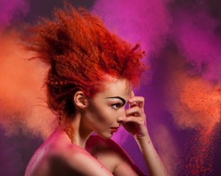 Beauty portrait of woman with color explosion made of color powder