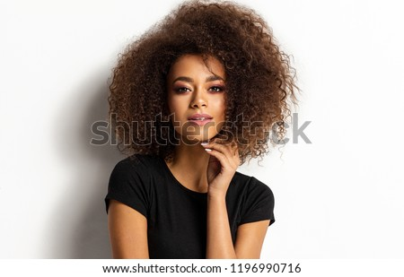 Beauty portrait of young adult african american woman with afro hairstyle looking at camera isolated on white background #1196990716