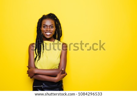 Beauty portrait of young african american girl posing on yellow background, looking at camera.