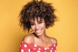 Beauty portrait of young african american girl with afro hairstyle. Girl posing on yellow background, looking at camera. Studio shot.