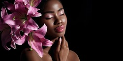 Beauty portrait of young African American model with pink art make up posing with lily flowers isolated on black background.