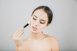 Beauty portrait of young, attractive, fresh, healthy and natural woman with the makeup brush