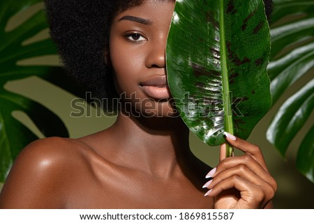 Beauty portrait of young beautiful african american woman with posing with banana leaf curly hair against green exotixc plants  background. Natural skin care concept