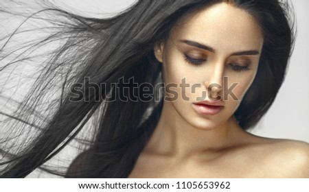 Beauty portrait of young beautiful brunette girl with long black straight flying hair. Vogue style. Magnificent hair.  #1105653962