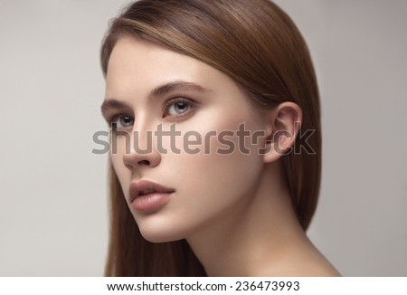 Beauty portrait of young beautiful sexy red-haired model with long straight hair. Professional nude makeup.