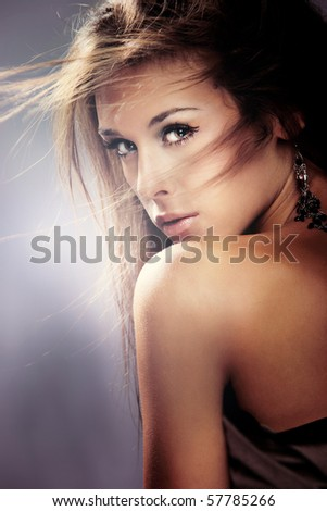 beauty portrait of young brunette woman, hair fly, studio shot