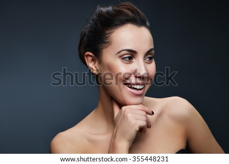 Beauty portrait of young caucasian brunette woman. Smiling and perfect skin. Natural nude makeup. Toned
