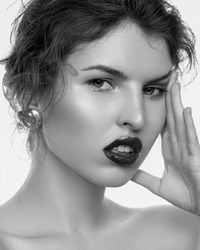 beauty portrait of young fashionable woman showing gorgeous trendy makeup posing with bare shoulders on white studio background black and white