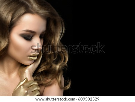 Stock Photo Beauty portrait of young woman with golden makeup. Perfect skin and fashion makeup with gold accents. Smokey eyes. Studio shot. Sensuality, passion, trendy luxurious makeup concept. Copy space