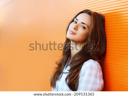 Beauty portrait pretty woman in the city summer near colorful wall