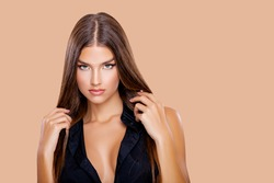 Beauty Portrait Young Woman holding her long natural brown Hair with her hands. Makeup. Brown-haired model with long hair posing over Beige background. Girl looking at camera. Eye make up